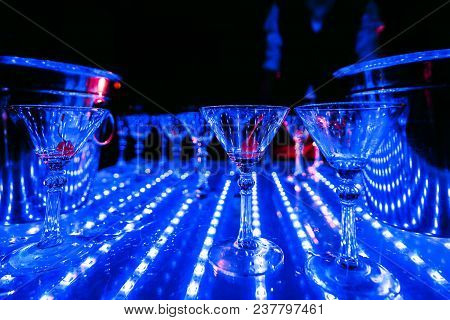 Empty Martini Glasses With Cherry On The Table At A Party With Blue Lights