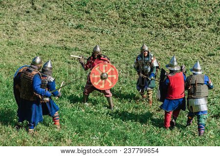Luh, Russia - August 27, 2016: Reconstruction Of Medieval Battle Of Knights In Armor And Weapons At