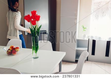 Woman Cooking Dinner In The Kitchen. Young Girl Opens Refrigerator To Get Some Food. Modern Kitchen