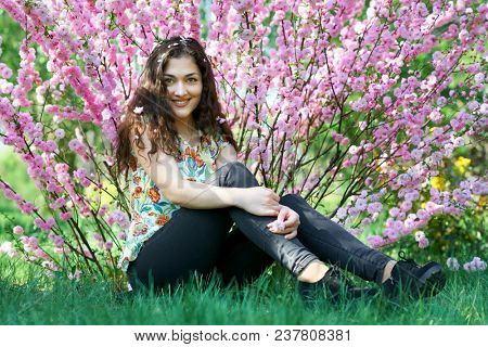 portrait of young girl on pink flowers background, sit on grass