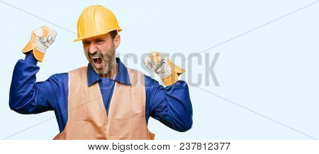 Senior engineer man, construction worker happy and excited celebrating victory expressing big success, power, energy and positive emotions. Celebrates new job joyful isolated over blue background