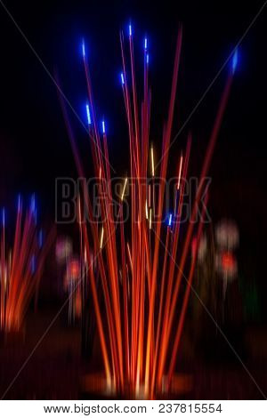 Artificial Giant Bamboo Plants And Flowers Decorated With Lights On Christmas Time. Night Background