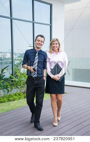 Full Length Portrait Of Two Business People Outdoors. Middle Aged Man And Woman In Formal Wear Havin
