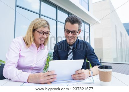 Two Smiling Business Colleagues Using Tablet At Cafe On Meeting. Mid Adult Man And Woman In Formal W