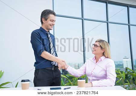 Two Smiling Business Partners Handshaking At Outdoor Office Cafe. Mid Adult Business Man And Woman S