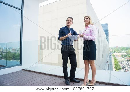 Two Smiling Business Partners Looking At Building Outdoors. Middle Aged Man And Woman In Formal Wear