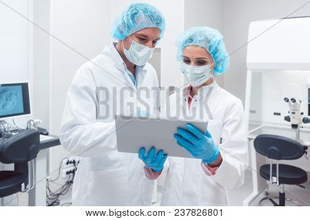 Two scientists working together in lab looking at data on a tablet computer