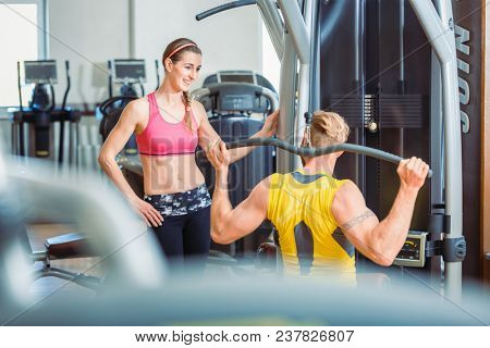 Fit beautiful woman smiling with admiration at a strong man exercising overhead lat pushdown at the cable machine in a trendy fitness club