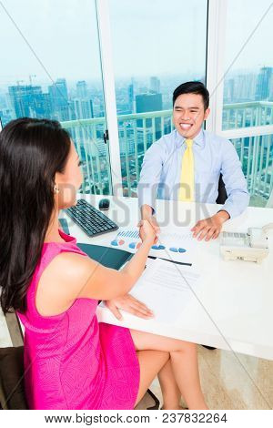 Cheerful Asian advisor with client on financial investment