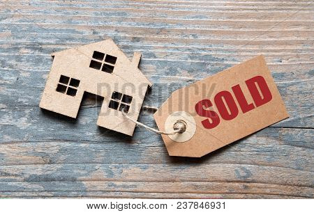 Small House With Sold Label Attached To It