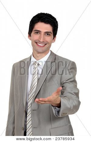 Portrait of an attractive businessman holding out his hand