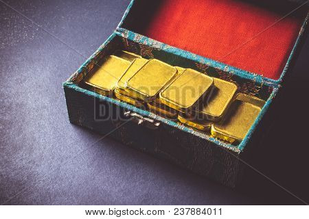 Close Up Of Pure Gold Bars In The Box On Dark Background.