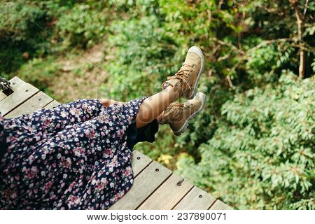 Cropped Image Of Woman Sitting On Wooden Footbridge In Jungle