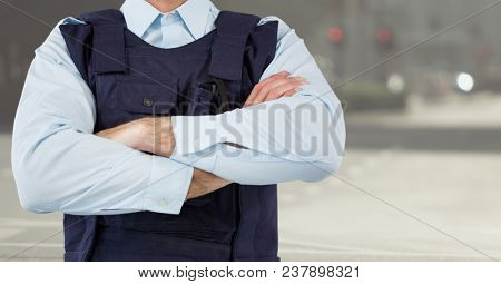 Digital composite of Security guard mid section arms folded against blurry street