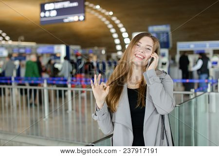 Female Person Talking By Smartphone At Airport Hall, Wearing Grey Coat And Black Bag, Showing Ok. Co