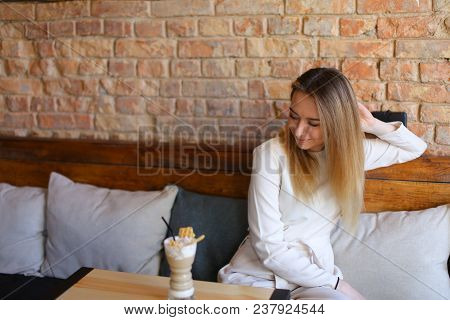 Cute Girl In Cafe, Young Beautiful Fair-haired Woman Wearing White Blouse, Grey Cloak And Blue Trous