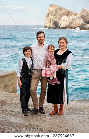 Portrait Of Cute Smiling Family In Retro Rural Old-fashioned Outfits Against The Sea Ocean Backgroun