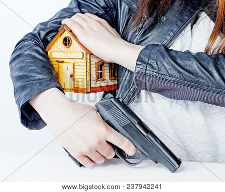 Armed Woman With A Gun In His Hand And A Toy House Under His Arm. The Right Of Armed Protection Of P