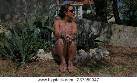 Beautiful Middle Aged Woman Sitting Between Aloe Vera Plants