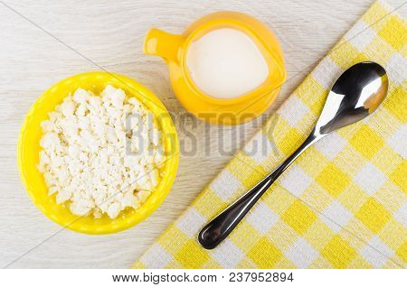 Granular Defatted Cottage Cheese In Plastic Bowl, Jug With Yogurt, Spoon On Checkered Napkin On Wood