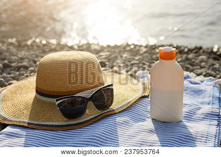Suntan Cream Bottle And Sunglasses On Beach Towel With Sea Shore On Background. Sunscreen On Deck Ch