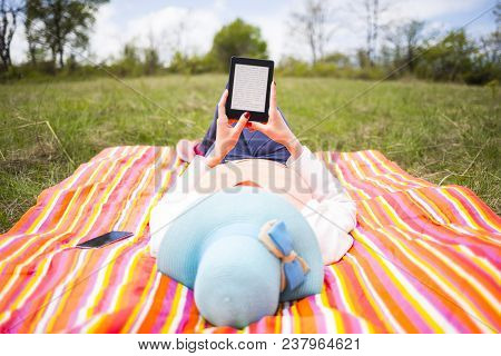 Young Woman With Blue Hat Dressed Casually Uses E-book/tablet Lying Down On A Colourful Blanket In T