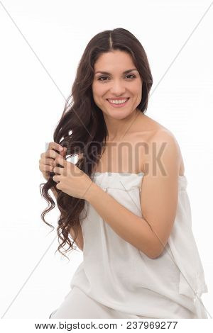 Half Length Image Of Sexy Brunette In White Dress Touching Her Healthy Curlu Hair. Beauty Concept. M