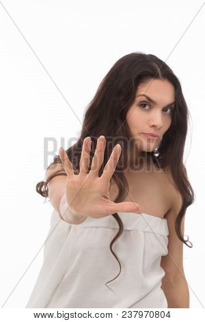 Nice Brunette Girl Showing Stop Sign In White Studio. Wearing White Dress. Mid Age Woman Over 35 Yea