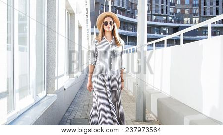 Young Woman In Sunglasses And Long Dress Walking On Street