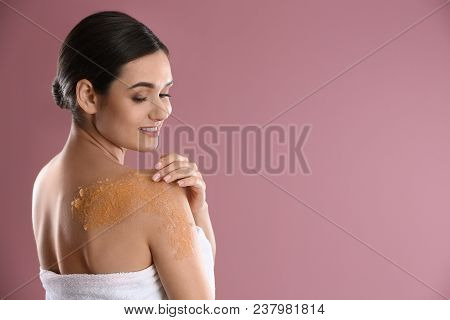 Young Woman Applying Natural Scrub On Her Shoulder Against Color Background