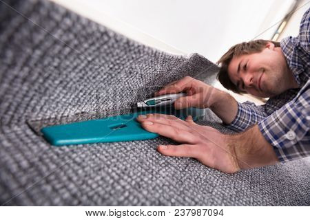 Male Carpet Fitter Installing Carpet With Cutter