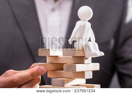 Human Figure Sitting On Top Of Stacked Wooden Blocks Being Arranged By Businessperson