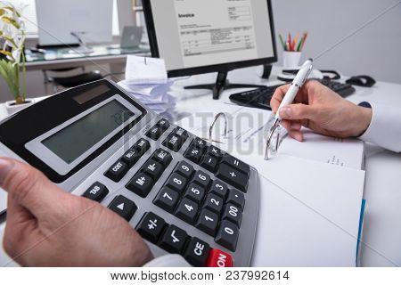Businessperson's Hand Calculating Bill