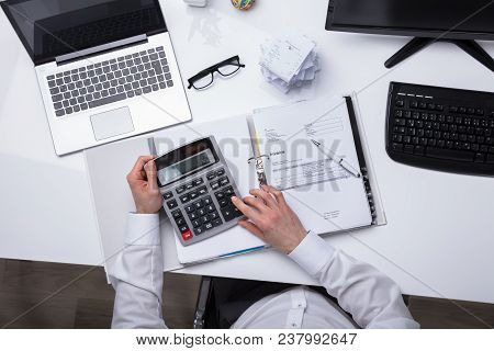 Elevated View Of Businessperson Calculating Invoice