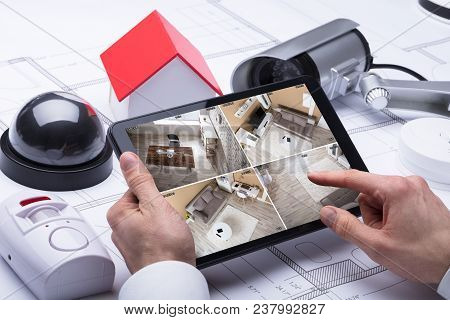A Person Watching Footage On Digital Tablet With Security Equipments And House Model On Blueprint poster