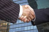 Businessmen in pinstripe suits shake hands with offices background. poster