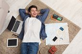 Young cheerful man dreaming about travel around world, lying on floor with blank laptop, tablet, smartphone, wallet and map at home. Handsome guy planning route of vacation, copy space poster