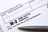 The pen lies on the tax form W-2 Wage and Tax Statement. The time to pay taxes poster