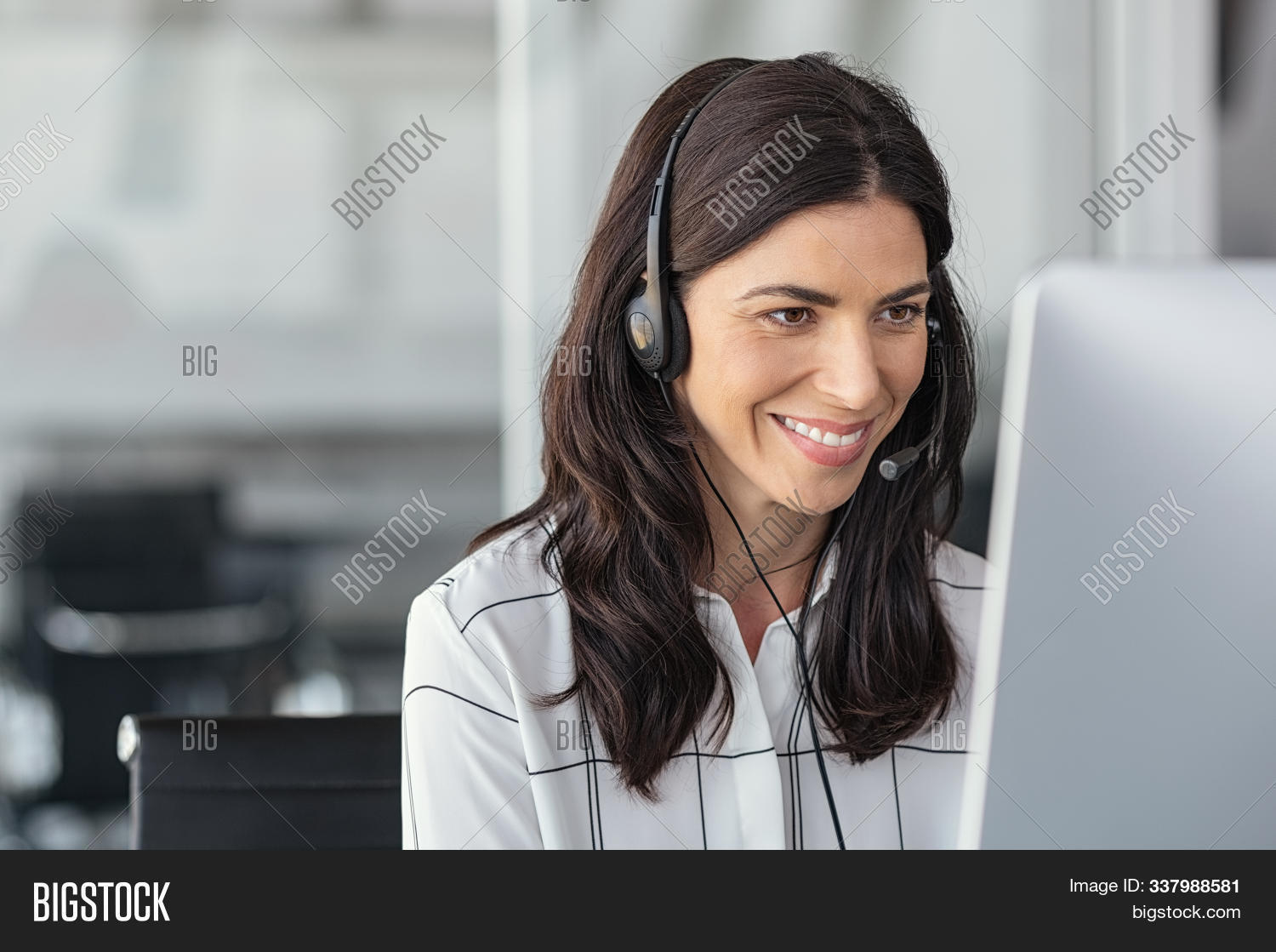 Call center business woman talking on headset. Portrait of mature woman working on computer in office. Smiling telephone operator with headset working on support customer service with copy space.