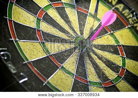 Dartboard And A Pink Dart Arrow Close To The Center. Reaching Goals Step By Step.