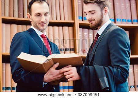 Two lawyers in the law firm discussing cases and precedents in front of bookshelf