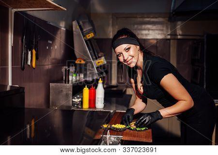 Woman Chef In The Kitchen Preparing A Hamburger Sandwich