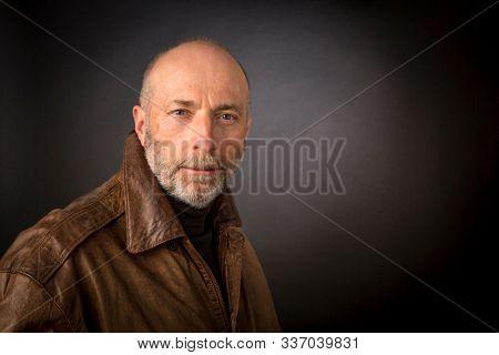 confident smirking senior man in leather jacket - an authetic headshot against a dark background
