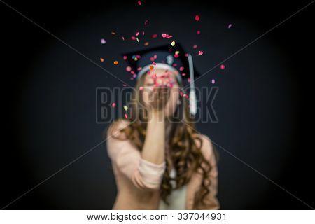 Graduatig Girl Blows Confetti In Black Background