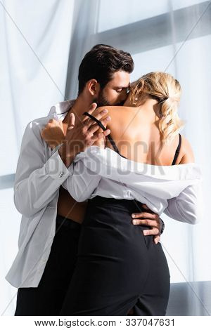 Business Couple Taking Off Clothes While Kissing In Office