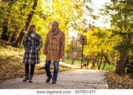 Happy Senior Couple Is Walking In Park In Autumn.