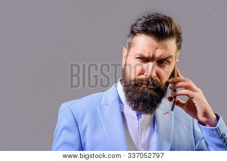 Serious Businessman Talking On Smart Phone. Stylish Business Man Calling With Telephone. Businessman