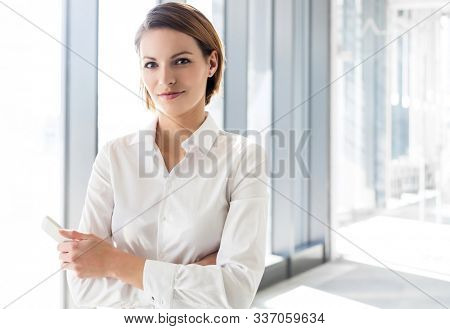 Young attractive businesswoman standing with arms crossed in office hall