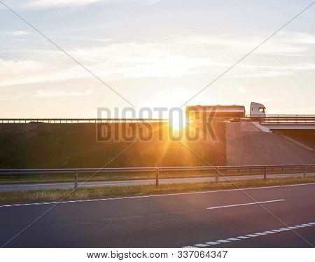 Truck Driver On A Large Truck With A Tanker Carries Cargo Against The Backdrop Of A Sunny Sunset, Co