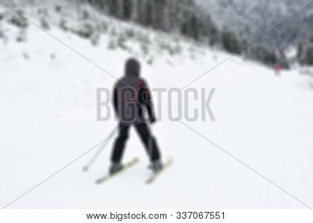 Slavske, Ukraine - December 23, 2019: Male Skier Skiing Downhill In High Mountains. Winter Landscape